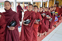 Myanmar, Burma.  Young Buddhist Monks Lined up to Receive Charitable Gifts from Wealthy Donor, Alodaw Pauk Pagoda, Nampan Village, Inle Lake, Shan State.
