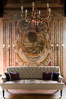 An elegant canape sofa backed by an original fresco on the wall succesfully restored