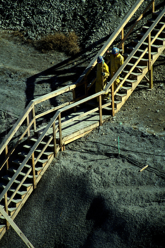 Two workers descend a wooden stairway at a construction job site. Construction workers.