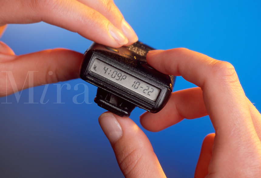 Hands holding a beeper.