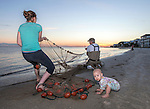 "Three generations of Wakulla County mullet fishermen John ""Cricket"" Taylor, right, his daughter Payton Taylor, left, and one year old granddaughter Natalie Holly make a strike at the beginning of the 2016 roe mullet run at Shell Point Beach in the Florida panhandle."
