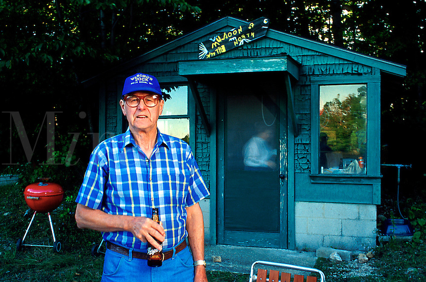 George at Muldoons. A senior man enjoys a bottle of beer while standing outside of a small bar or restaurant. Gills Rock, Wisconsin.