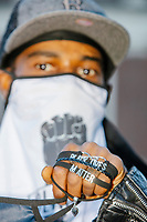 A man sells Black Lives Matter facemasks, shirts, shoes, and jewelry as protestors gather near the statue of Samuel Adams outside Faneuil Hall at the end of the 2020 Women's March protest in opposition to the re-election of US president Donald Trump in Boston, Massachusetts, on Sat., Oct. 17, 2020.