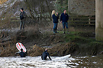 Surfers leaving the water after a poor Severn Bore at Overbridge, Glos in the early morning sunshine. The bore was five star rated, which means the biggest of the year, fueled by the large spring tides that push up the River Severn Estuary..