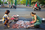 Woman Cleaning Fish On Street