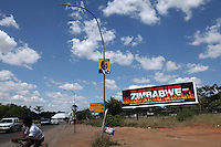 An election poster for Jacob Zuma and his African National Congress (ANC) party in front of a billboard calling for democracy in Zimbabwe, in the border town of Musina.