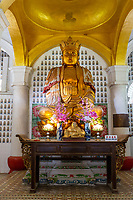 Chinese Buddha in the Ban Po Thar Pagoda, Kek Lok Si Buddhist Temple.  Small Smiling Buddha in foreground. George Town, Penang, Malaysia.
