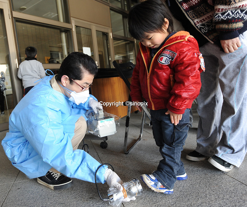 A child is tested for radiation in Fukushima City, Japan, 60 km from the Fukushima Daiichi Nuclear Power Plant and with-in the 80 km exclusion zone.  The nuclear Plant was damaged during the  Earthquake and following Tsunami that struck Japan 11th March 2011..17 Mar 2011