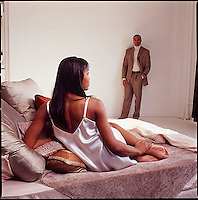 African American woman lounging on couch with man in background against wall<br />