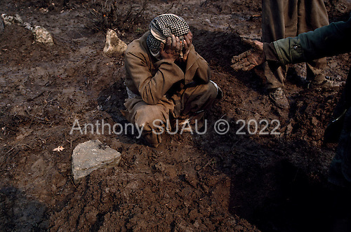 Isikveren, Turkey.April 12, 1991..At one of three camp grave sights a father weeps for his loss at sunrise. The mountain top Kurdish refugee camp became home to an estimated 300,000 refugees after they fled Saddam Hussein's post Gulf war persecution...In the wake of the 1991 Persian Gulf War rebellions in Southern and Northern Iraq occurred. The uprising in the Kurdish areas of Northern Iraq broke out in March, sparked by demoralized Iraqi Army troops returning from it's defeat against United States lead coalition forces in southern Iraq and Kuwait. Although they presented a threat to Iraqi President Saddam Hussein?s regime, his Iraqi Republican Guard suppressed the rebellion with massive force, as the expected US intervention never materialized. ..The faltering rebellion fueled a terrified mass exodus. The U.N. High Commissioner for Refugees called it the largest in its 40?year history. During March and early April, nearly two million of Iraqis escaped from strife-torn cities to the mountains along the northern borders and into Turkey and Iran. Their exodus was sudden and chaotic, with thousands fleeing on foot, on donkeys, or crammed onto open-backed trucks and tractors. Thousands, many of them children, died or suffered injury along the way, primarily from adverse weather, unhygienic conditions and insufficient food and medical care. Some were killed by army helicopters, which deliberately strafed columns of fleeing civilians. Others were injured when they stepped on land mines planted by Iraqi troops near the Iran border during the war. Greenpeace has estimated that at one point in 1991, an estimated 2,000 Kurds were dying every day..