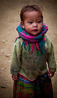 A little too young for school, this child in a village outside of Sapa watches older children walk to school.