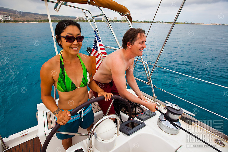 A couple navigating a sailboat on the west side of Oahu