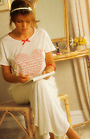 Young woman in nightdress writing letter