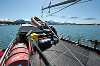 Captain David Janka pushes on his red Zodiac skiff as he prepares to stow it on the M/V Auklet, while at anchor in Heather Bay, Prince William Sound, Southcentral Alaska on a sunny spring day in early May. MR/PR