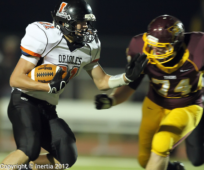 HARRISBURG, SD - OCTOBER 23:  Dereck DeVries #21 from Lennox prepares to be hit by Carson Creel #74 from Harrisburg in the first quarter of their 11A first round playoff game Tuesday night at Harrisburg. (Photo by Dave Eggen/Inertia)