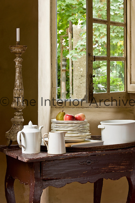 A pile of cream plates and an antique church candlestick are stored on a table beneath an open window