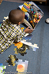 Educaton preschool 4-5 year olds boy working on floor puzzle vertical looking at illustration on box as a guilde to putting puzzle together