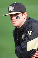 Conor Keniry (14) of the Wake Forest Demon Deacons watches from the dugout during the game against the Marshall Thundering Herd at Wake Forest Baseball Park on February 17, 2014 in Winston-Salem, North Carolina.  The Demon Deacons defeated the Thundering Herd 4-3.  (Brian Westerholt/Four Seam Images)