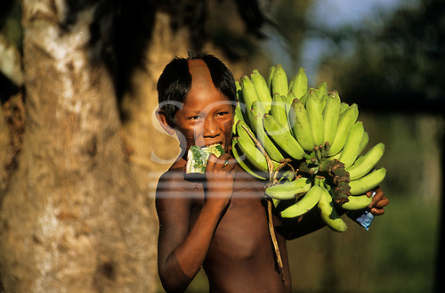 Bacaja village, Brazil. Indian boy holding a bunch of bananas and eating watermelon; Xicrin Indian tribe, Amazon.