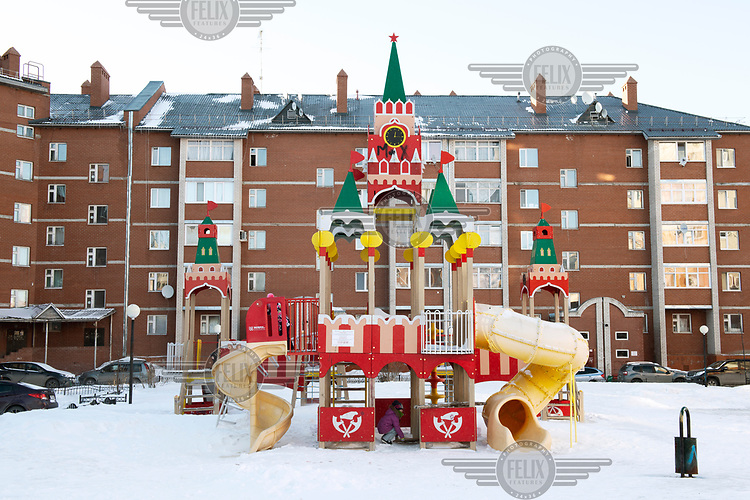 A children's playground with a slide in the shape of the Kremlin tower in the grounds of a housing estate.