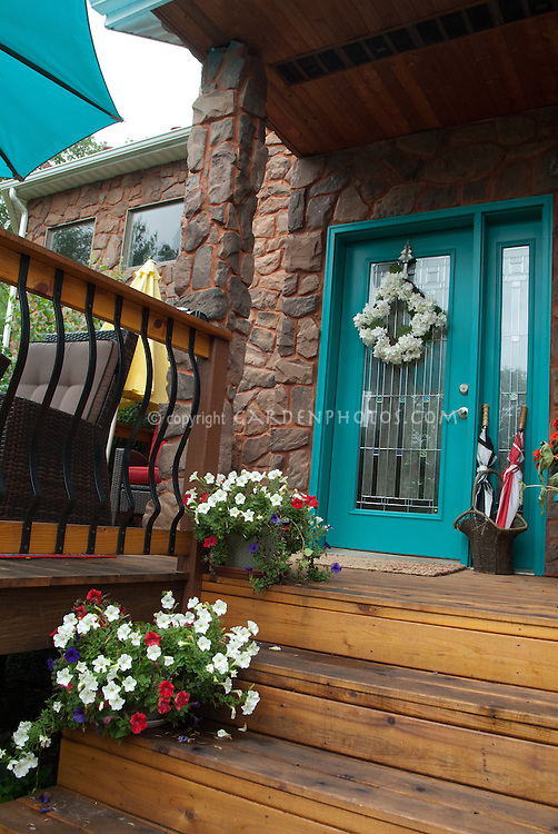 Front entranceway porch pretty, matching color planter containers and front door paint, impatiens, statues, umbrella stand, stone wall