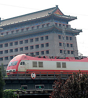 Train passes by city of Beijing, China. The ancient building at the back is the Southeast Corner Tower of Beijing City Wall..30 Aug 2010