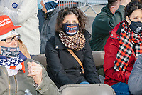 People wearing Trump campaign clothing, including MAGA hats and Trump-themed facemasks wait in the audience for the arrival of US President Donald Trump at a Make America Great Again Victory Rally in the final week before the Nov. 3 election at Pro Star Aviation in Londonderry, New Hampshire, on Sun., Oct. 25, 2020.