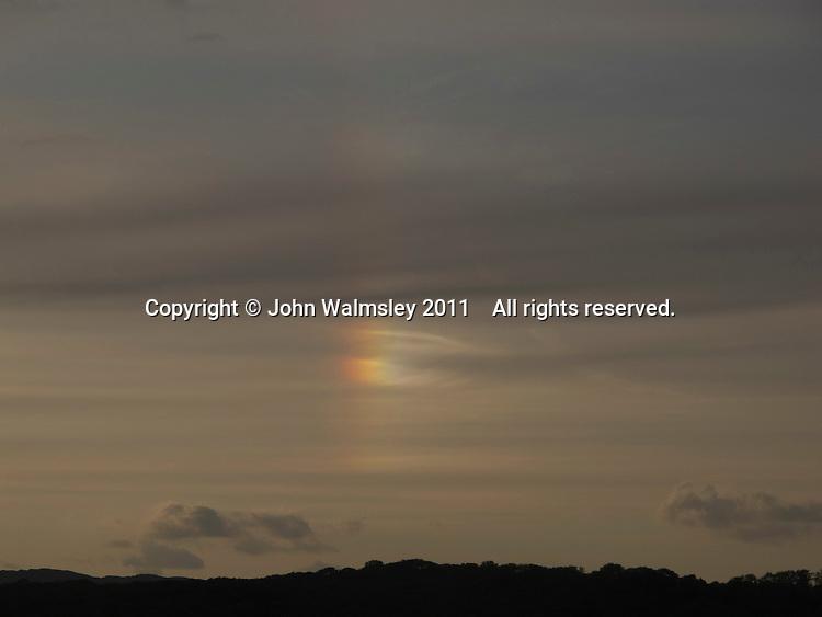 Rainbow cloud at dusk over the River Kent, Arnside, Lancashire, UK.