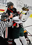 28 January 2012: University of Vermont Catamount forward Brett Bruneteau, a Graduate from Omaha, NB, is pushed back by Northeastern University Huskies' forward Ludwig Karlsson, a Freshman from Stockholm, Sweden, as Assistant Referee Charles Hanafin breaks the two up at Gutterson Fieldhouse in Burlington, Vermont. The Catamounts, dressed in their Breast Cancer Awareness jerseys, fell to the Huskies 4-2 in the second game of their 2-game Hockey East weekend series. Mandatory Credit: Ed Wolfstein Photo