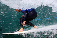 A surfer is barrelled in a wave.
