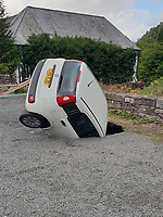 "Pictured: The white Fiat Panda car which ended up inside a sinkhole in the car park of Craig Y Nos castle in Wales, UK. Saturday 18 August 2018<br /> Re: A car has fallen into a sinkhole in the car park of Craig Y Nos castle in the Brecon Beacons, Wales, UK.<br /> Luke Davies was surprised when he got a call from his father asking him to go up to the castle where his mother was working.<br /> He went under the impression that it was not that serious.<br /> The hole was about 18-20 feet at its deepest, and the car had fallen in bonnet-first and was wedged against the other side of the hole.<br /> ""It must have happened within five to 10 minutes, Mr Davies, 30, from Coelbren in Powys, said.<br /> A visitor had seen it happen and alerted staff, who told his mother, Karen.<br /> The general manager managed to attach a tow rope to the car to prevent it from falling further.<br /> It is thought that the sinkhole has been caused by an underground stream of water, possibly leading to erosion under the overflow car park.<br /> Once the recovery vehicle arrived, they considered using a crane as they were concerned about further damaging the car.<br /> The door panels were damaged and one of the rear doors couldn't be opened."