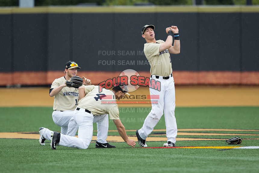 Wake Forest Demon Deacons right fielder Keegan Maronpot (13) follows through on his golf swing as teammates Stuart Fairchild (4) and Jonathan Pryor (11) look on following their 8-4 win over the Georgia Tech Yellow Jackets at David F. Couch Ballpark on March 26, 2017 in Winston-Salem, North Carolina.  The Demon Deacons defeated the Yellow Jackets 8-4.  (Brian Westerholt/Four Seam Images)