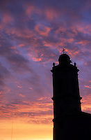 Church tower silhouetted at sunset, Piana, Corsica, France.