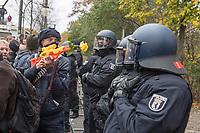 """Sogenannten """"Querdenker"""" sowie verschiedene rechte und rechtsextreme Gruppen hatten fuer den 18. November 2020 zu einer Blockade des Bundestag aufgerufen. Sie wollten damit verhindern, dass es eine Abstimmung ueber das Infektionsschutzgesetz gibt.<br /> Es sollen sich ca. 7.000 Menschen versammelt haben. Sie wurden durch Polizeiabsperrungen daran gehindert zum Reichstagsgebaeude zu gelangen. Sie versammelten sich daraufhin u.a. vor dem Brandenburger Tor.<br /> Im Bild: Ein Demonstrant zielt mit einem Spielzeuggewehr in dem eine Rose steckt, vor einer Polizeiabsperrung auf der Strasse des 17. Juni auf die Beamten.<br /> 18.11.2020, Berlin<br /> Copyright: Christian-Ditsch.de"""