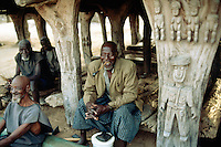 """Mali. Province of Mopti. Koporo-Pen. Dogon land. 20 km away from the bottom of the Bandiagara cliff.  Village life. Old men sit in  the """"Tougouna"""" which is traditionnaly used by elders for reunion. The Tougouna's wood pillars are decorated with symbolic sculture from the dogon art. © 2003 Didier Ruef"""