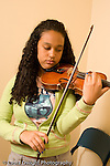 Middle School grade 8 music education girl playing violin during lesson vertical