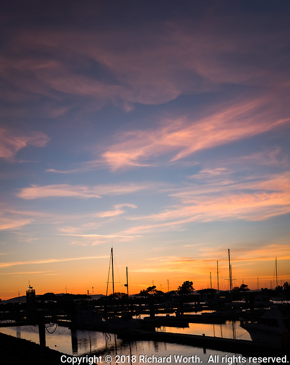 A quiet sunset with wispy clouds and a glowing horizon over sailboats floating in a marina.   Four image vertical panoramic.