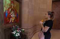 """Armenia. Yerevan. Lilit Martirosyan is praying at St Anna church, which is part of the Armenian Apostolic Church. She is a transgender woman and a civil rights activist fighting for the rights of trans people in Armenia. Lilit Martirosyan is the founder and the president of the NGO called """"Right Side"""", founded in 2016 to defend and fight for the rights of the trans community in Armenia. She became on April 5th 2019 the first member of her country's lesbian, gay, bisexual, transgender and intersex (LGBTI) community to deliver a speech on the parliamentary podium, speaking out against discrimination at a session of its committee on human rights. A trans woman (sometimes trans-woman or transwoman) is a woman who was assigned male at birth. Trans women may experience gender dysphoria and may transition; this process commonly includes hormone replacement therapy and sometimes sex reassignment surgery, which can bring immense relief and even resolve gender dysphoria entirely. Yerevan, sometimes spelled Erevan, is the capital and largest city of Armenia. The Armenian Apostolic Church is the national church of the Armenian people. Part of Oriental Orthodoxy, it is one of the most ancient Christian communities. Mary was a first-century BC Galilean Jewish woman, and the mother of Jesus, according to the New Testament. 1.10.2019 © 2019 Didier Ruef"""