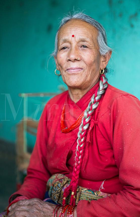 Nepal. Nepali weaving woman, posing and weaving threads for carpets. Nayapati, Eastern Kathmandu.  43