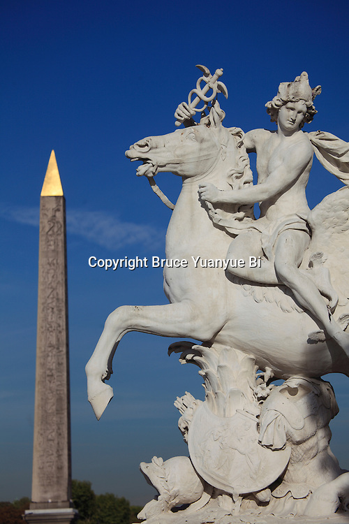 The statue of Mercury riding Pegasus decorated the west entrance of Tuileries Garden with the Obelisk in Place de la Concorde in background . City of Paris. Paris