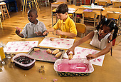 MR / Schenectady, New York. Howe International Magnet School (urban public magnet school with international theme) / Second grade Students (aged 7, two are African-American) stamp potato prints using paint they made from natural materials (beets and cornstarch). MR: CN-gr2-CR ©Ellen B. Senisi