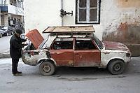 Azerbaijan. Baku Region. Baku. Downtown. Town center. A man fills with gas the petrol tank of an old rusty Lada car parked on a concrete road. Plastic bottle.  © 2007 Didier Ruef