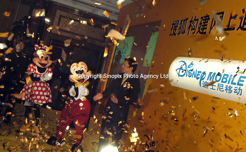 Sohu.com Inc. Chairman and founder Charles Zhang & Disney characters Mickey Mouse & Mini Mouse celebrate the launching of Desney.com.cn during a press conference in Beijing, China. Walt Disney Co., the second-largest U.S. media company, said Sohu.com Inc. will distribute Disney brand content to cellular phone users in China. Sohu.com will also provide design and hosting for Disney's China Web site..30-OCT-03