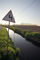 Binasco (Milano), Parco Agricolo Sud. Un cartello stradale indicante doppia curva e un canale d'irrigazione lungo un campo agricolo --- Binasco (Milan), Rural Park South. A road sign indicating a double curve and a drainage ditch along an agricultural field