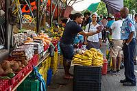 Willemstad, Curacao, Lesser Antilles.  Fruit Vendor Offering Grapes to Policeman-Customer.