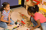Preschool 4 year olds two girls discussing problem while playing with toy trains
