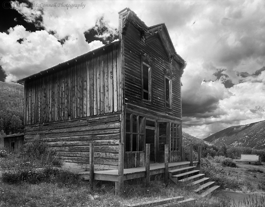 """""""Ashcroft Hotel""""<br /> Ashcroft Ghost Town <br /> Aspen, Colorado <br /> 2011<br /> <br /> Erected in the early 1880's, the original building was a hotel, Chinese restaurant, and brothel.  The gingerbread trim on the upper level is original indicating that the hotel facade was more elaborate.  Ornamental trim, matching the gingerbread design, was once evident at the midsection of the building.  This is one of the false fronted buildings in Ashcroft.  The shack at the back of the hotel was the domain of the Chinese chef, who according to legend, had a dispute with the brothel's Madame and fled to the hills.<br /> <br /> 4 x 5 Large Format Film"""