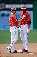 Batavia Muckdogs manager Mike Jacobs (17) congratulates Jerar Encarnacion (27) after hitting a triple during a game against the Lowell Spinners on July 15, 2018 at Dwyer Stadium in Batavia, New York.  Lowell defeated Batavia 6-2.  (Mike Janes/Four Seam Images)