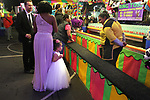 A young girl looks to be overwhelmed by the ring toss at the Mill Valley Memorial Day Carnival.