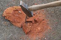 Stein wird mit dem Hammer zerkleinert, um buntes Gesteinsmehl zu erhalten, mit dem sich eine schöne Farbe anmischen lässt, Kinder malen mit selbstangemischten Erdfarben, Farbe aus verschiedenfarbiger Erde,